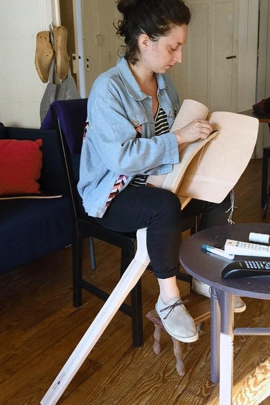 Couture du cuir à la main avec une grande pince en bois posée à terre
